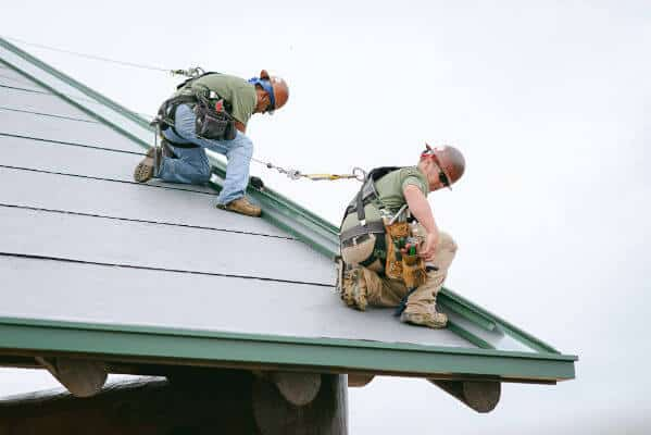 Mid-South Roof Systems sheet metal workers atop roof pitch workiing and maintaining roof safety