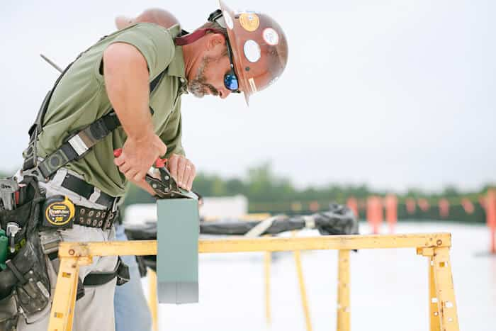Mid-South Roof Systems sheet metal worker atop roof working