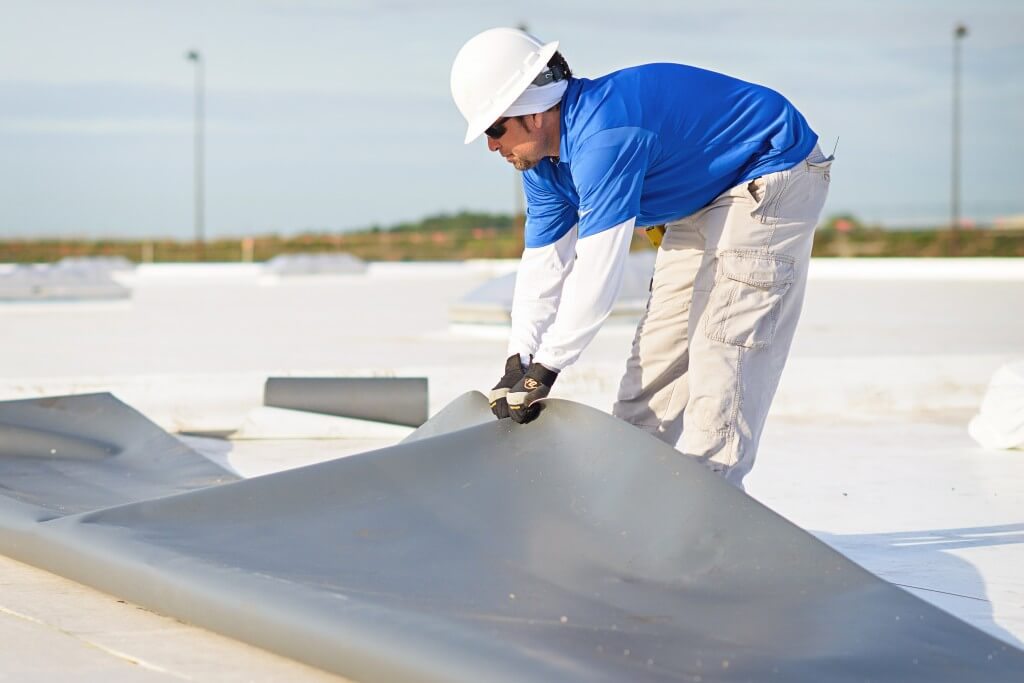 Mid-South Roof Systems Team Members atop a roof working on flat roof material