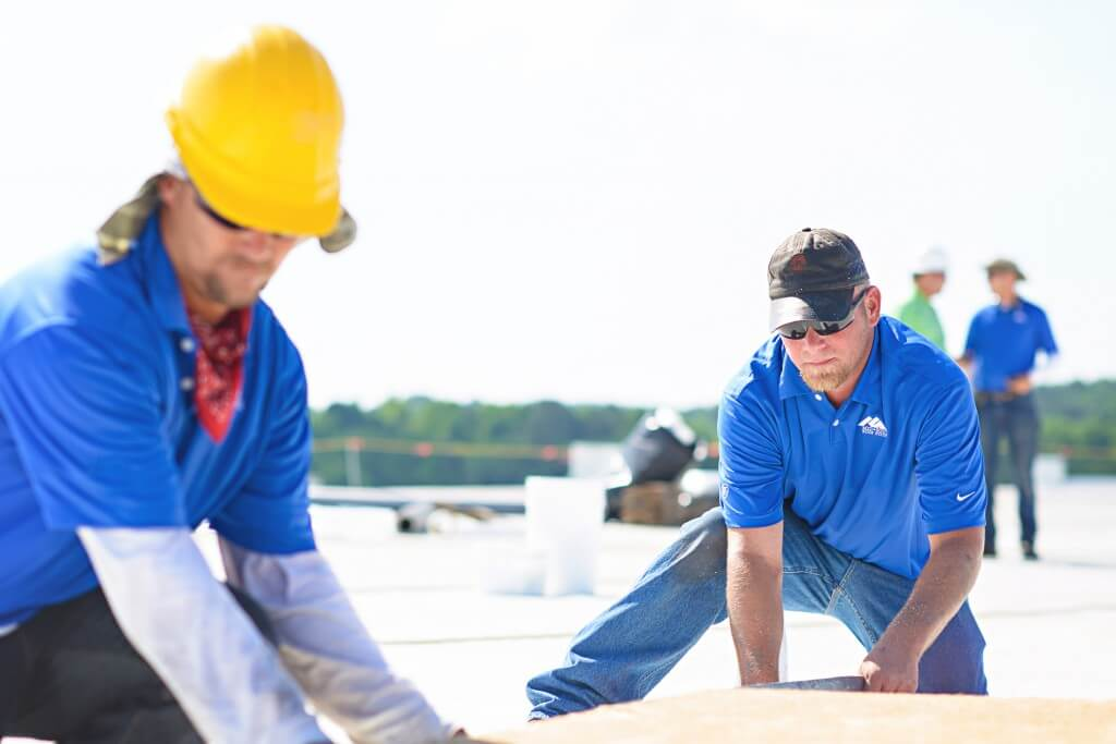 Mid-South Roof Systems Team Members atop a roof working on commercial roof leak