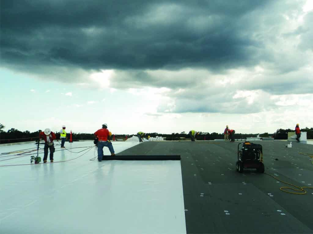 Mid-South Roof Systems Team Members atop a roof working on water damage