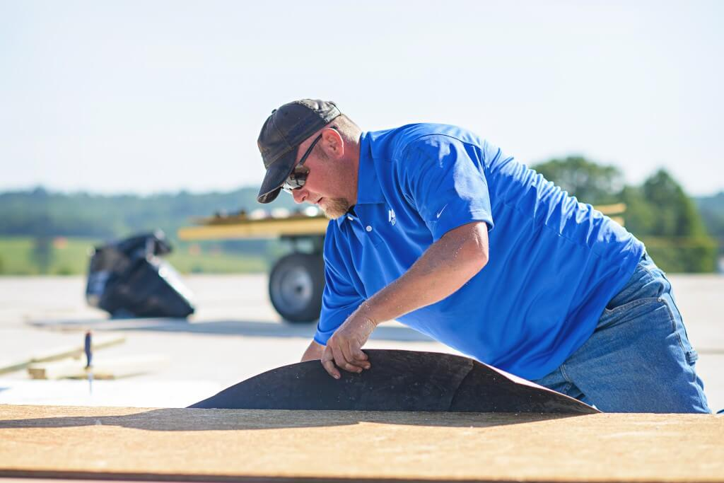 Mid-South-Roof Systems team member working on Walk Pads commercial roof