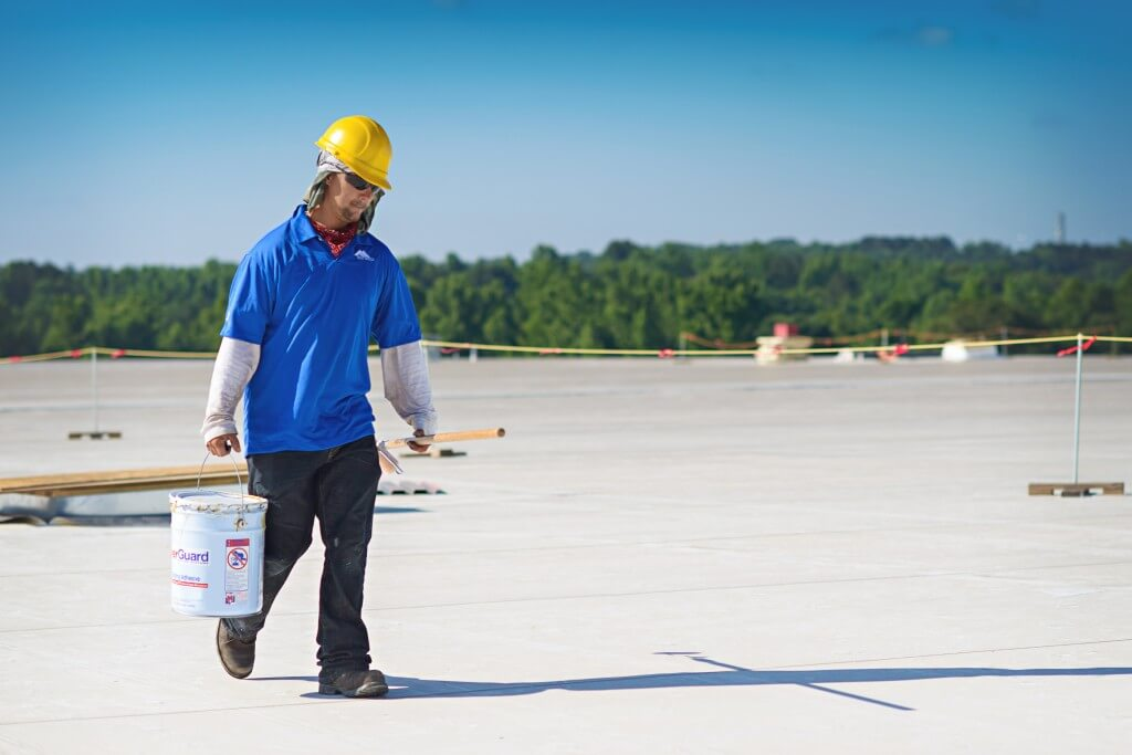Mid-South Roof Systems worker carrying bucket, commercial roof warranties