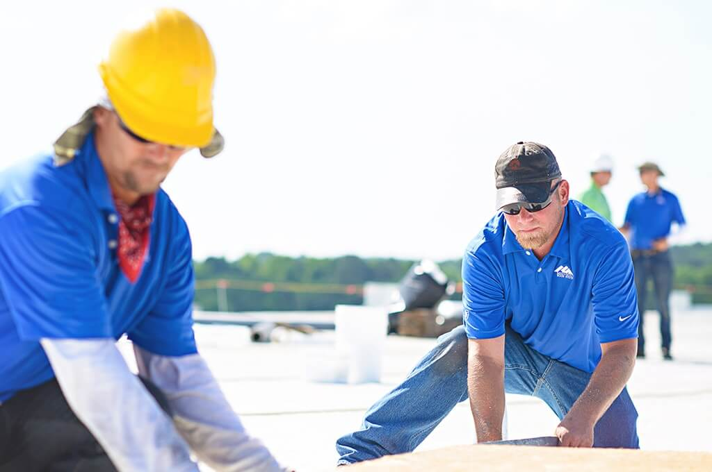 Two Mid-South Roof Systems Team Members atop a roof working