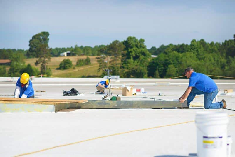 Mid-South Roof Systems Team Members atop a roof doing roofing work